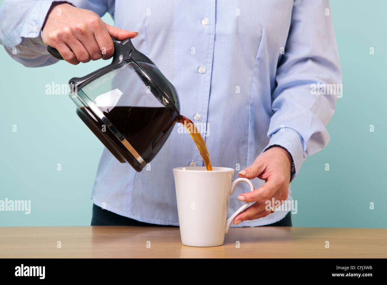 Photo of a woman on her break pouring herself a mug of hot filtered coffee from a glass pot. - Stock Image
