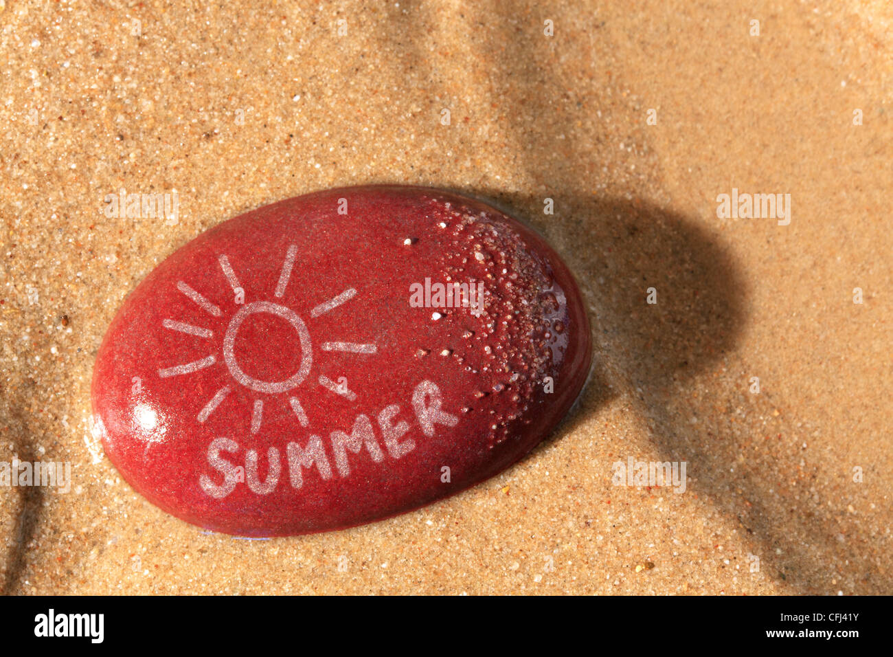 Concept photo of a wet red pebble on a sandy beach with a drawing of the sun and the word summer on it - Stock Image