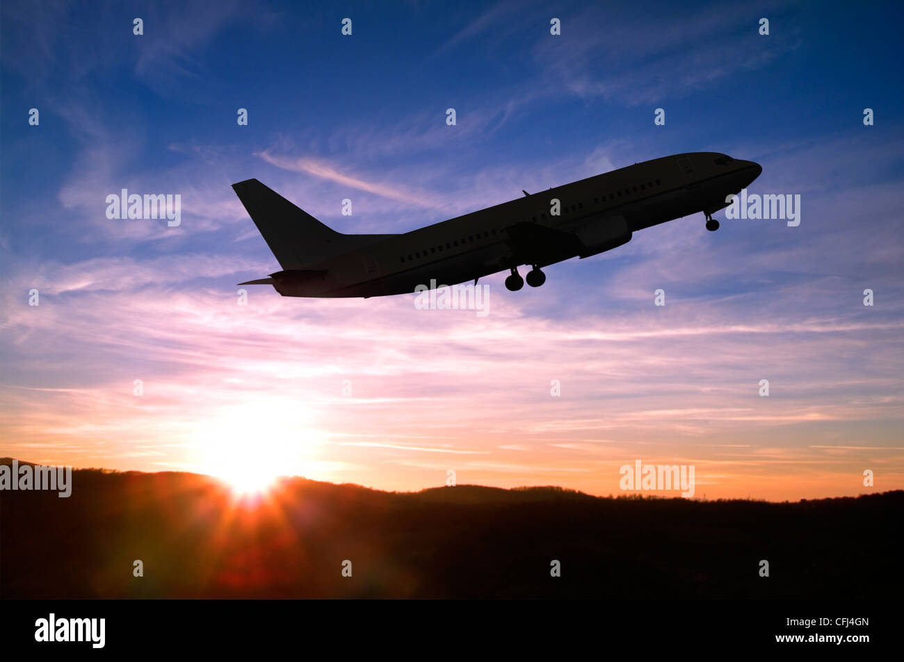 Airplane Taking Off into a Sunset. - Stock Image
