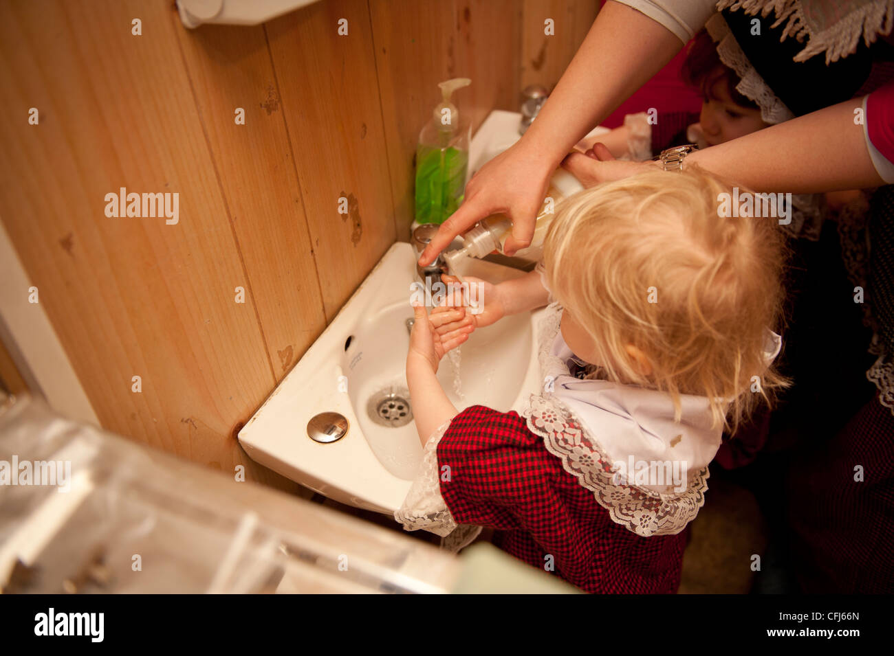 a child washing her hands at a nursery school kindergarten pre-school playgroup  wales UK - Stock Image
