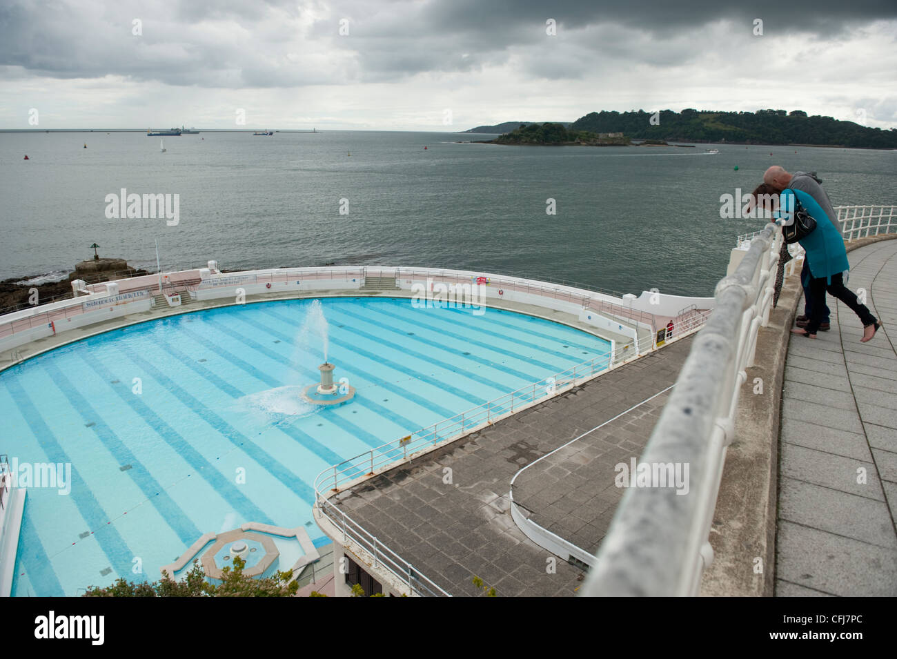 A couple lean over a railing to see the Tinside Lido outdoor swimming pool in Plymouth. - Stock Image