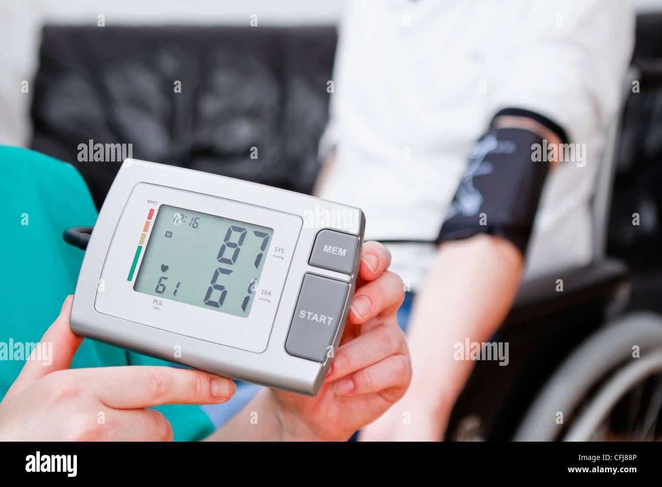 Blood pressure check for young adult in wheelchair. - Stock Image