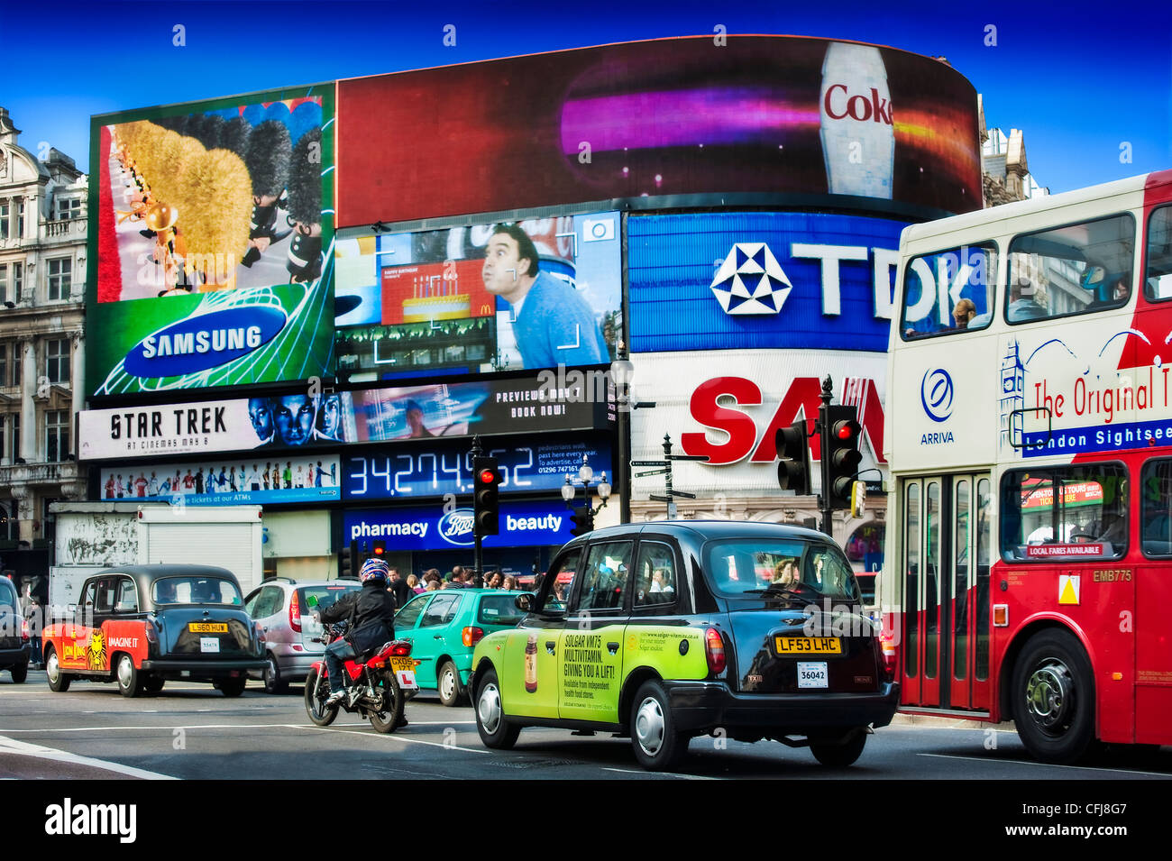 London buses and cabs early evening rush hour, Piccadilly Circus, London West End. - Stock Image