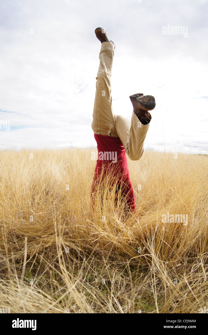 Young girl doing headstand in a filed of long grass - Stock Image