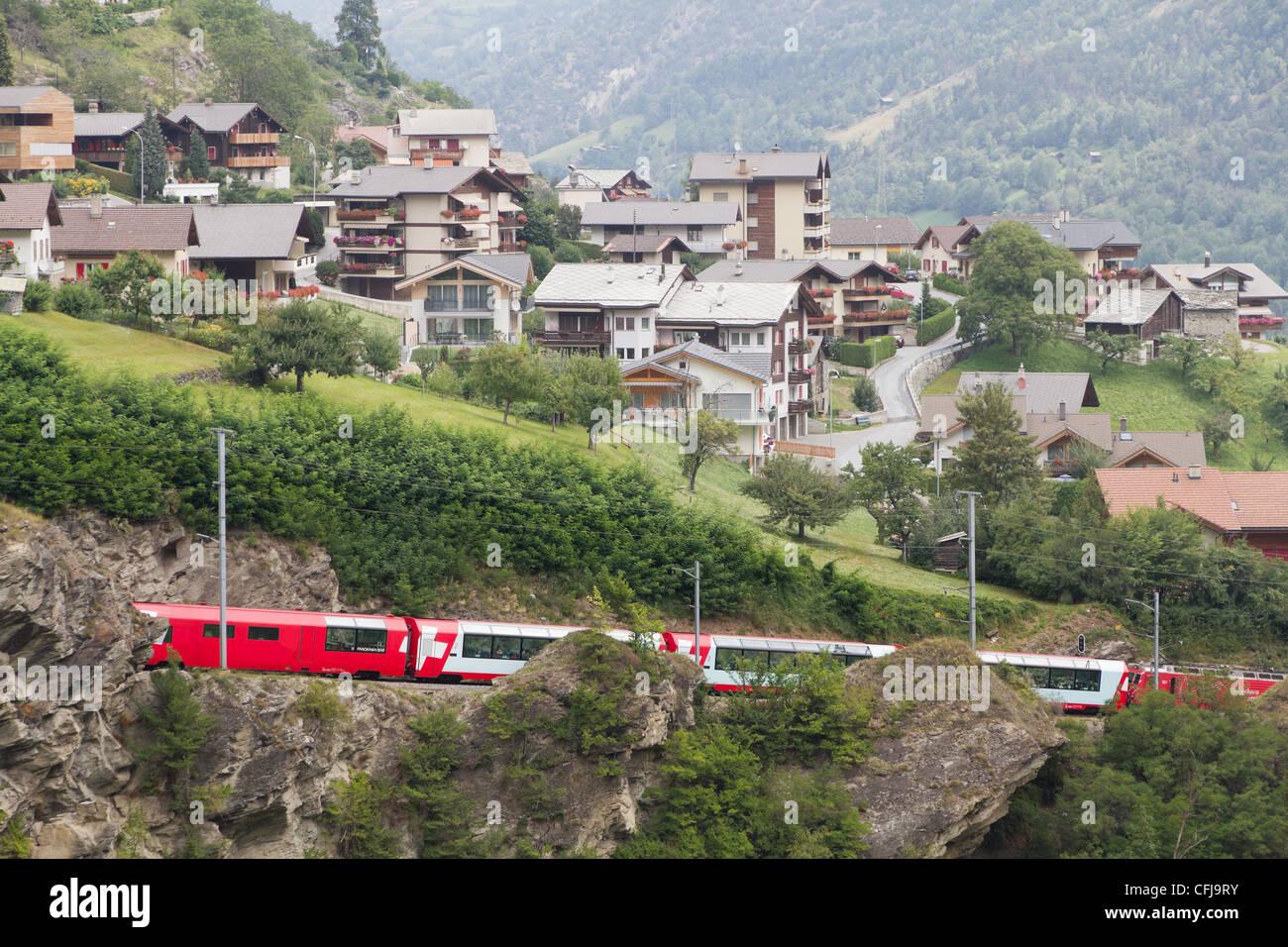 Glacier express train passes village, Switzerland - Stock Image