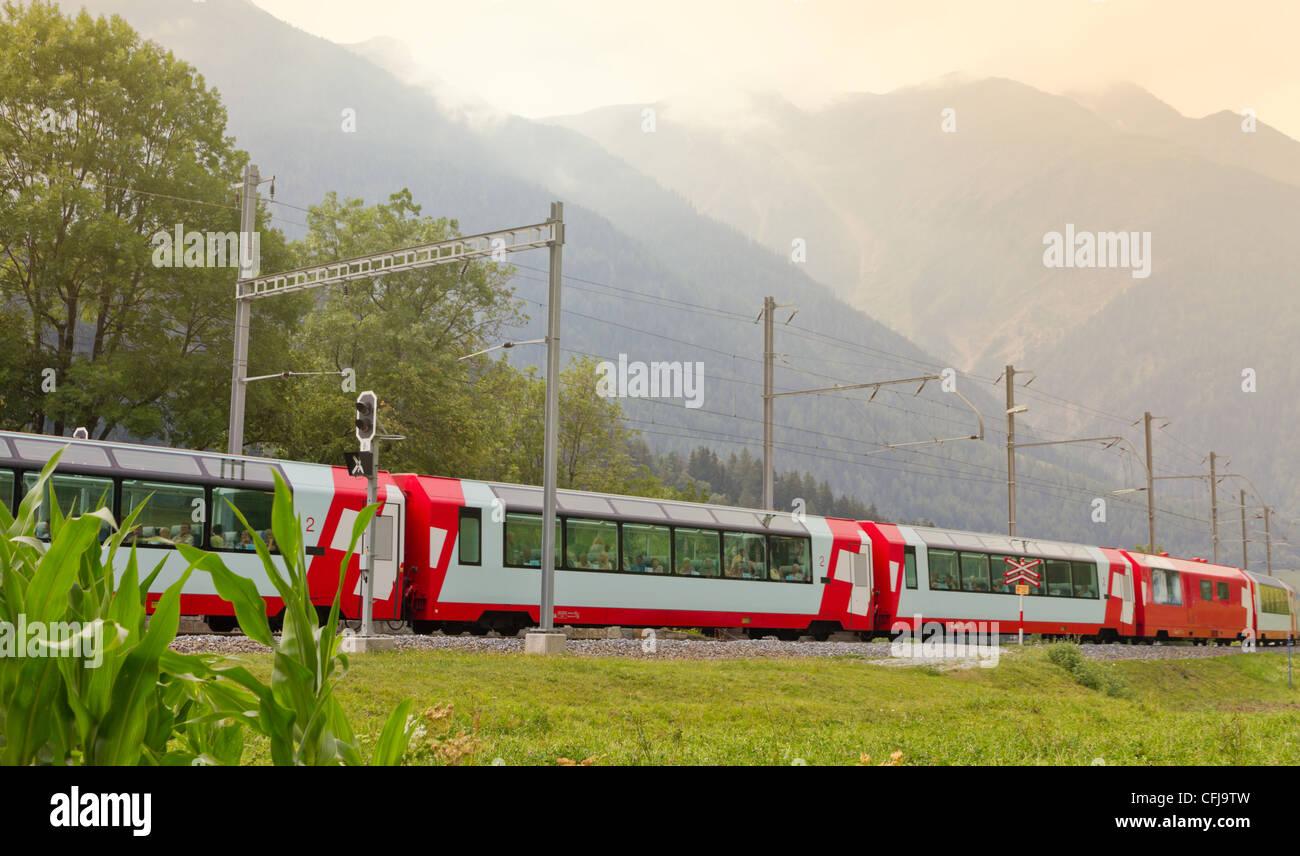 Glacier express train passes high mountain valley, Switzerland - Stock Image