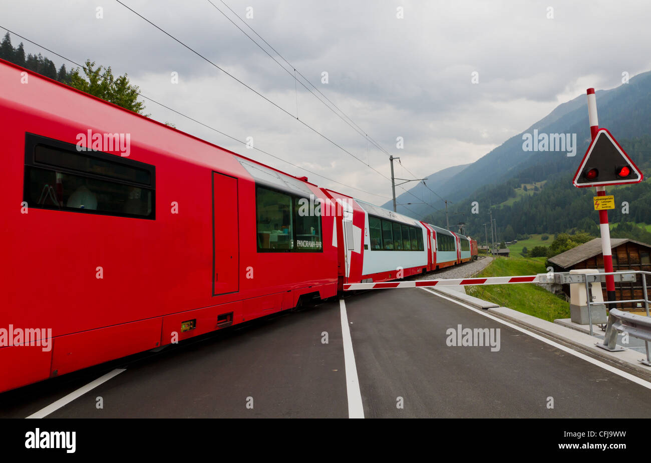 Glacier express train crosses road with closed railway crossing gate, Switzerland - Stock Image