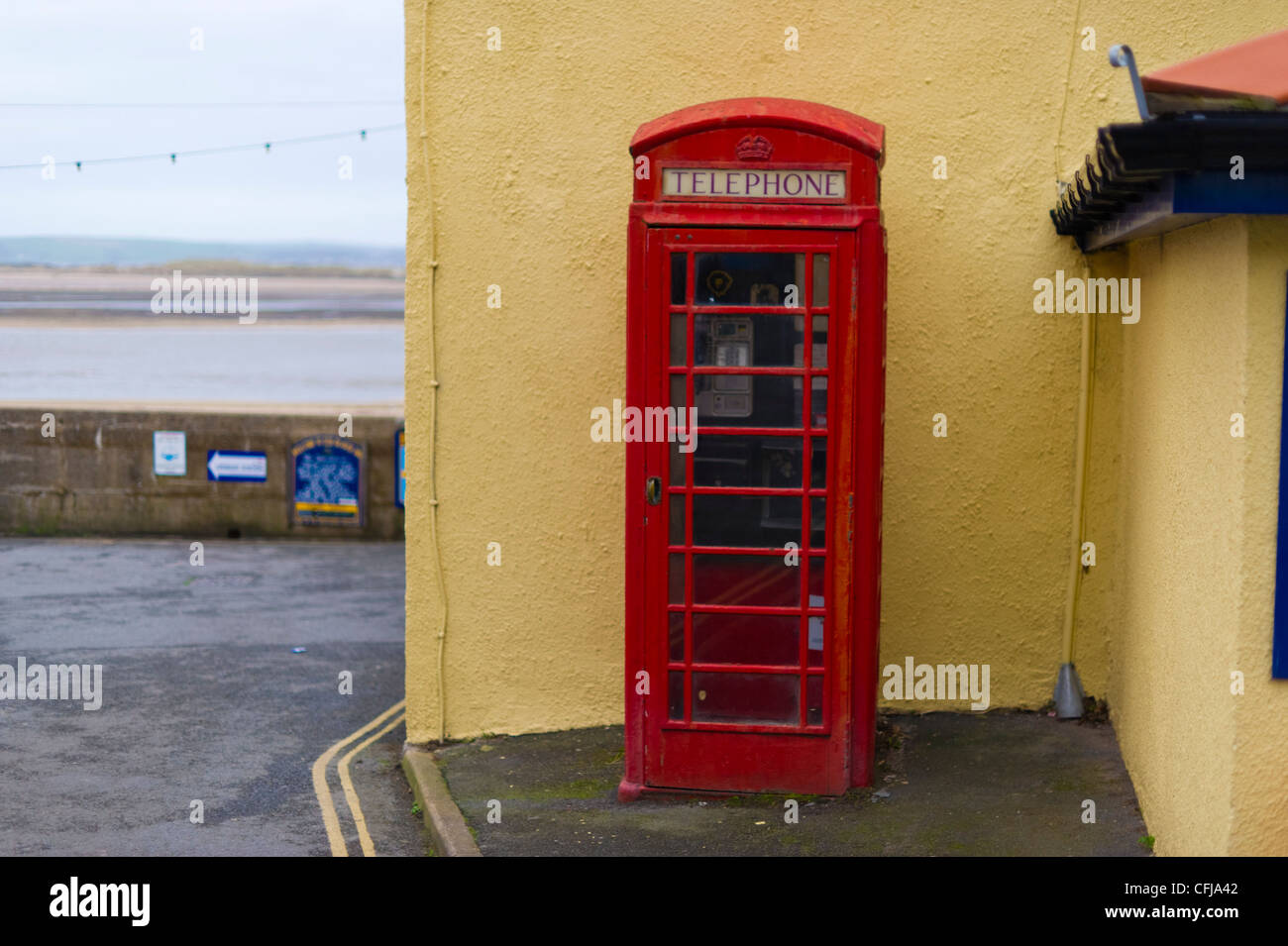 A traditional red telephone box in the Devon village of Appledore next to the waterfront. - Stock Image
