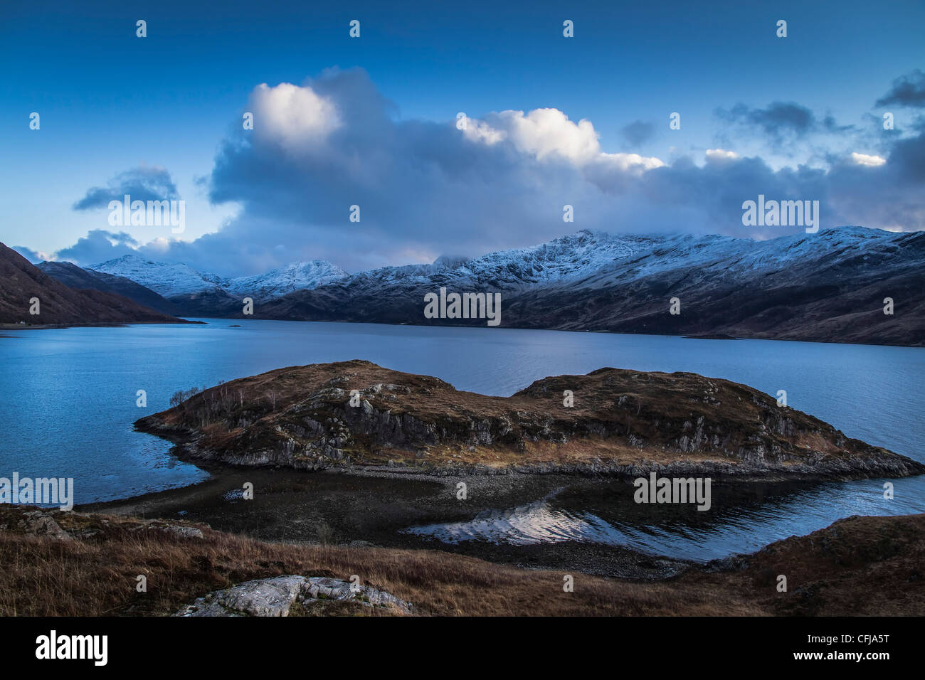 Island in Loch Hourn Arnisdale Scottish Highlands with snow covered mountains of the Isle of Skye in the background - Stock Image