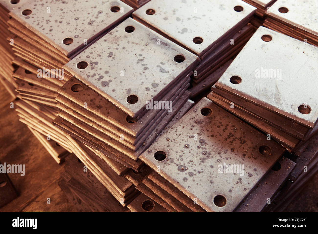 Grunge rusty rectangle metal plates with round holes placed on wooden textured board - Stock Image
