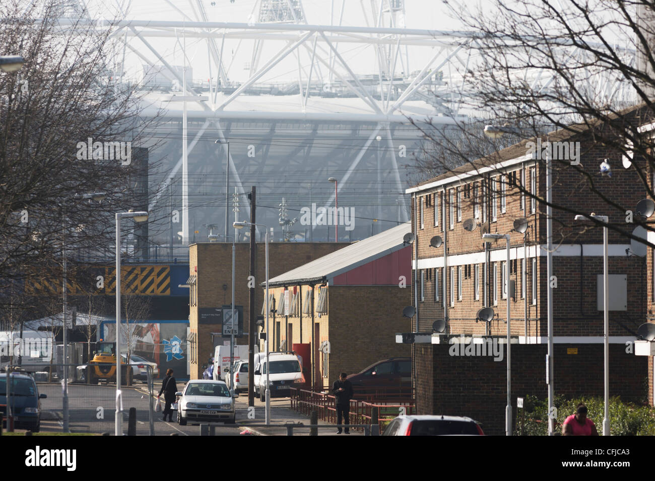 East London housing and the 2012 Olympic stadium that dominates the end of a street of a nearby estate. - Stock Image
