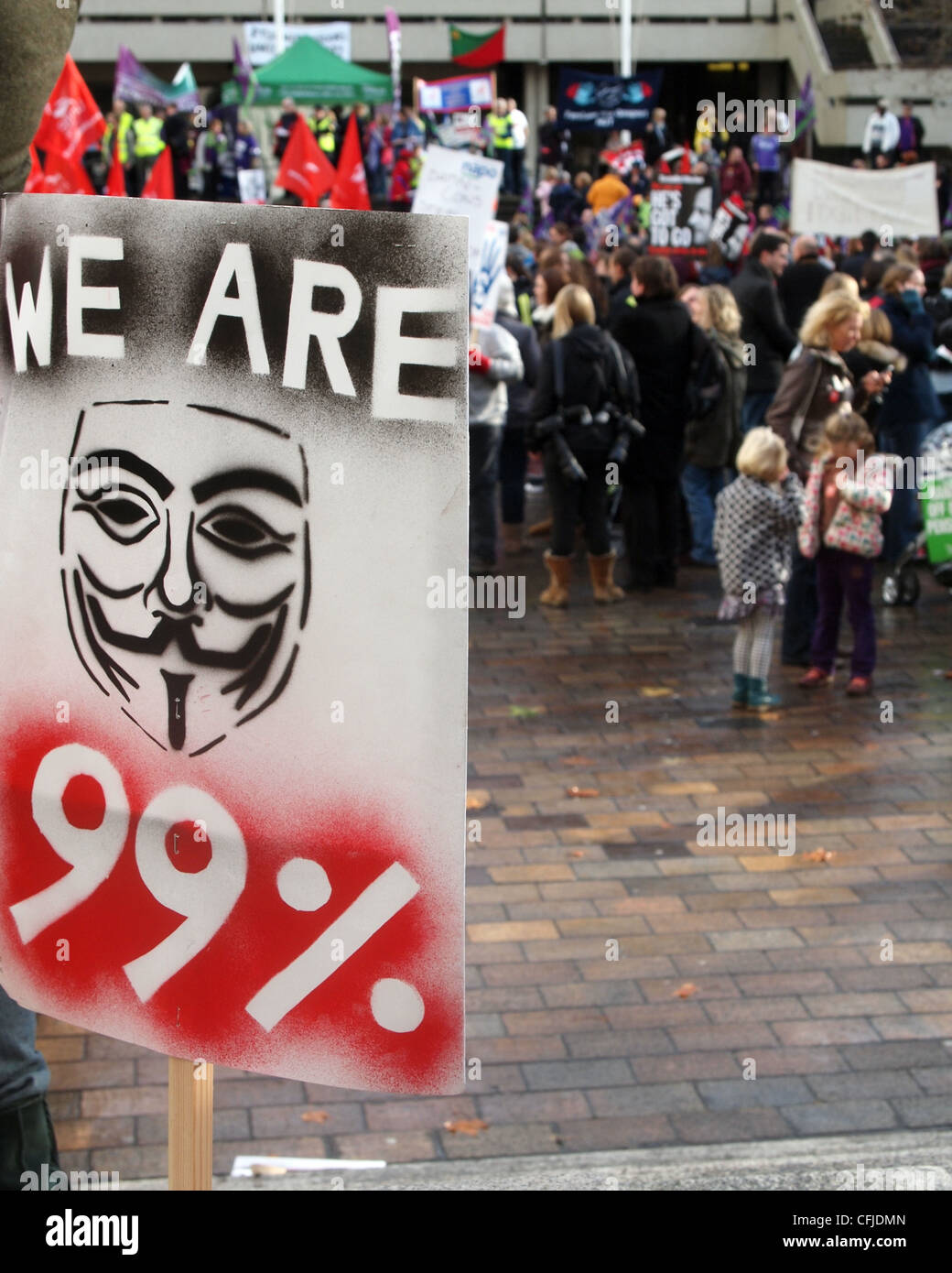 We are 99% placard with the guy Fawkes mask symbol and protesters in the background - Stock Image