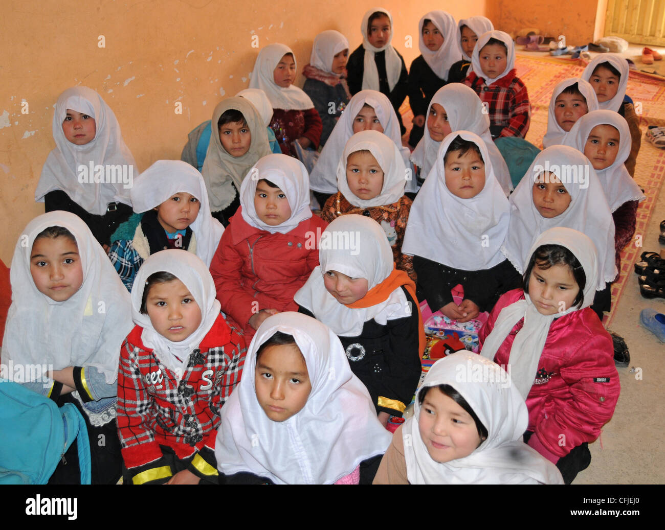 Young Afghan girls sit for classes on the hallway floor of the Aliabad School near Mazar-e-Sharif, Afghanistan - Stock Image