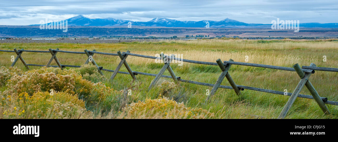 Buck and rail fence, with grasslands of Warner Wetlands Area of Critical Environmental Concern and Hart Lake, Hart - Stock Image