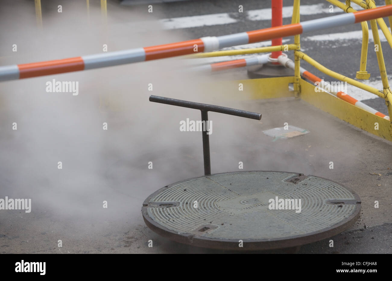 Roadworks with manhole cover and steam - Stock Image