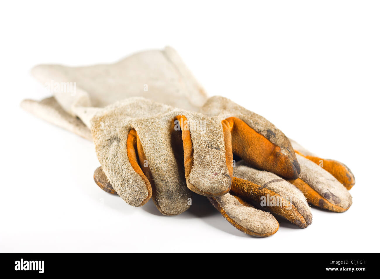 Dirty old leather gloves shallow focus isolated on white background - Stock Image