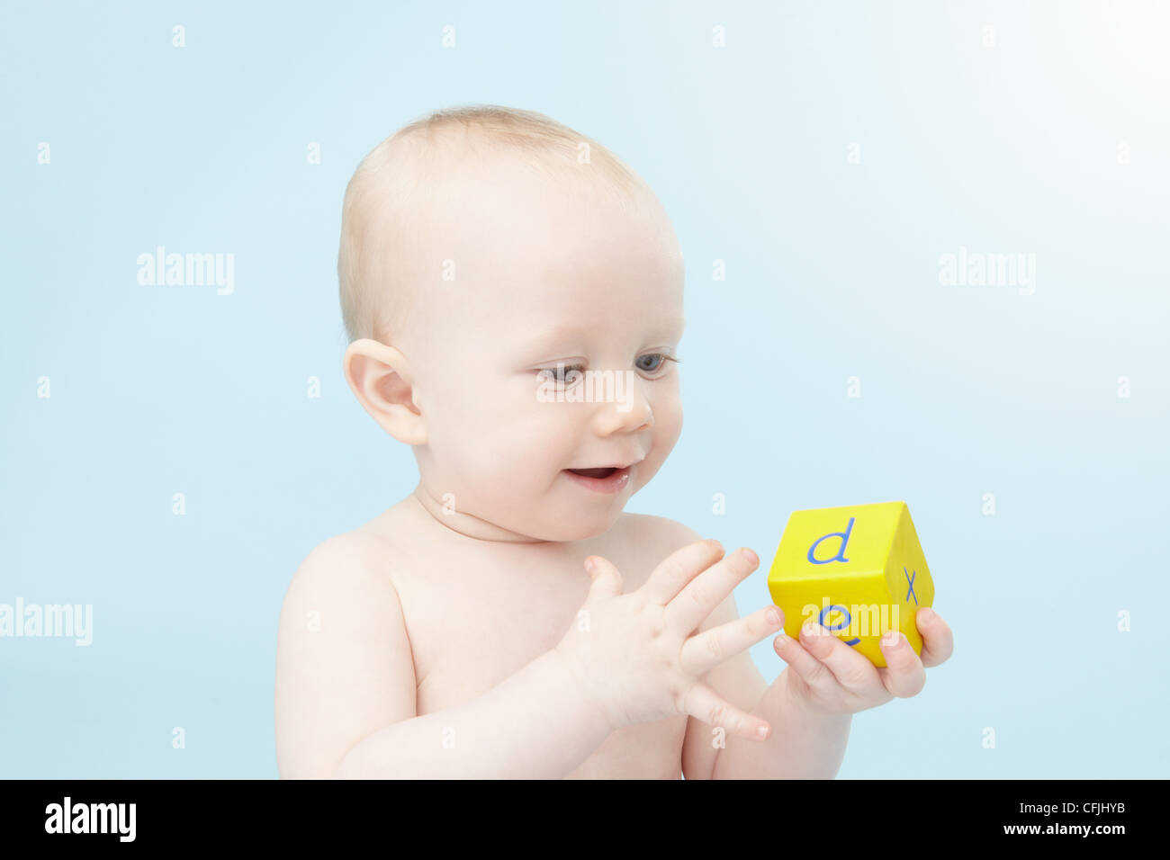 Baby looking at alphabet cube - Stock Image