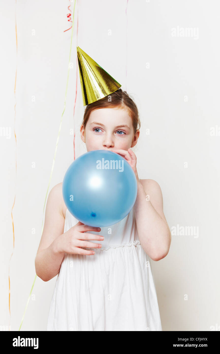 Girl in party hat, blowing up balloon - Stock Image