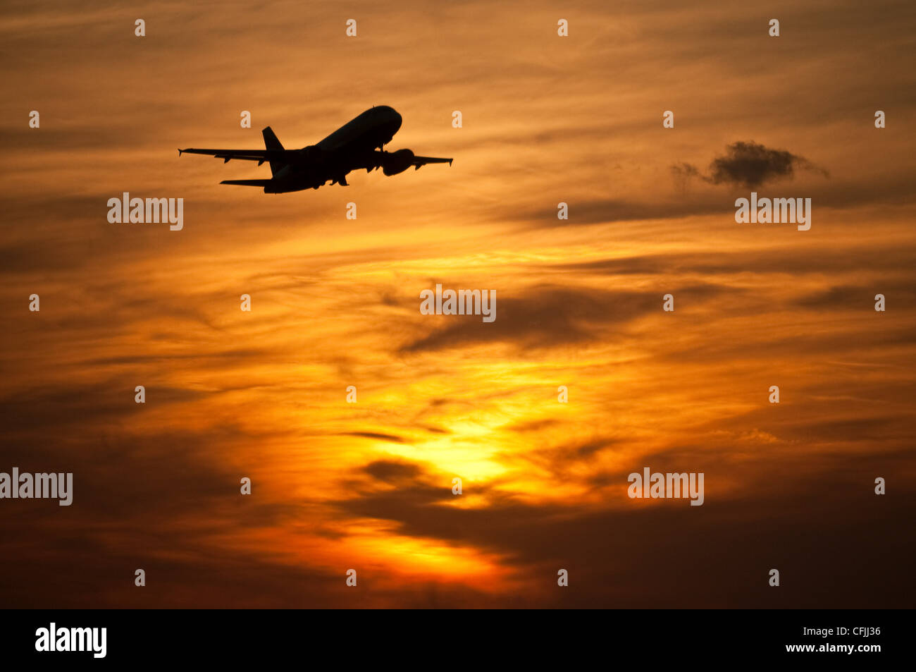 Airplane in in evening sky - Stock Image