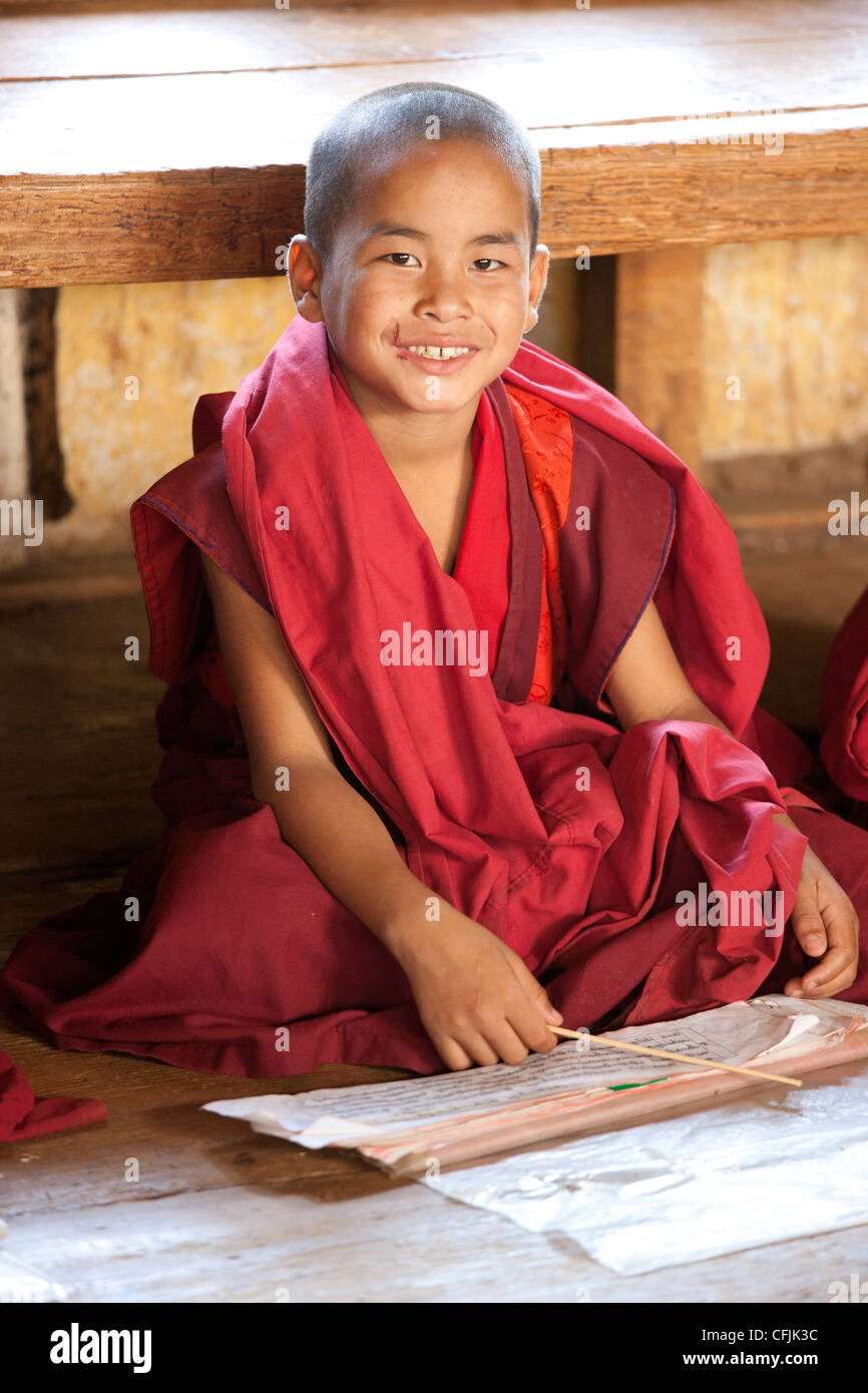 Young Buddhist monk studying scripts in class at Chimi Lhakhang Temple, Punakha Valley, Bhutan, Asia - Stock Image