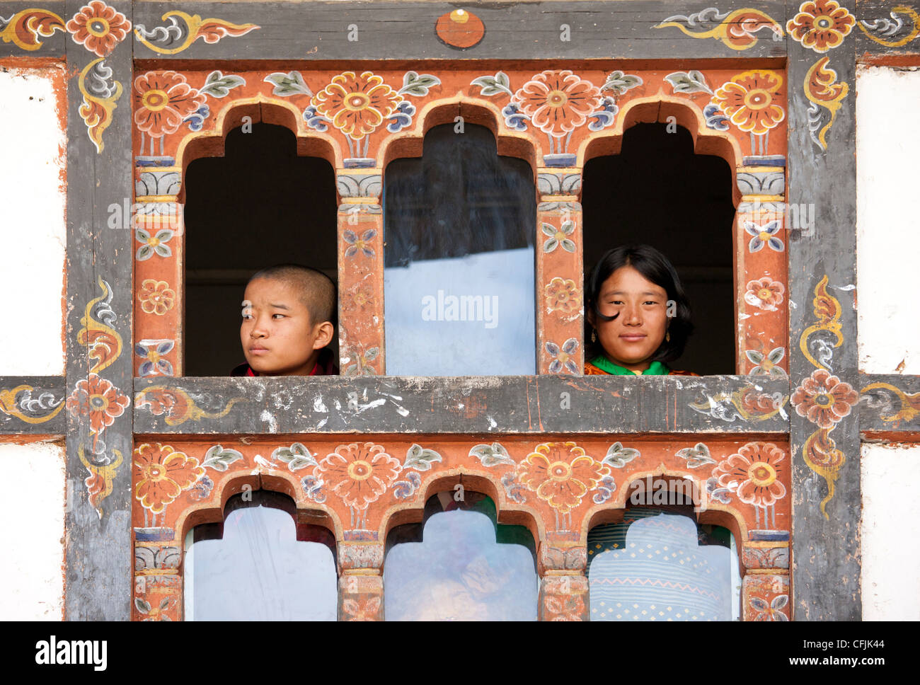 Girl and boy looking out of windows, Wangdue Phodrang (Wangdi), Bhutan, Asia - Stock Image