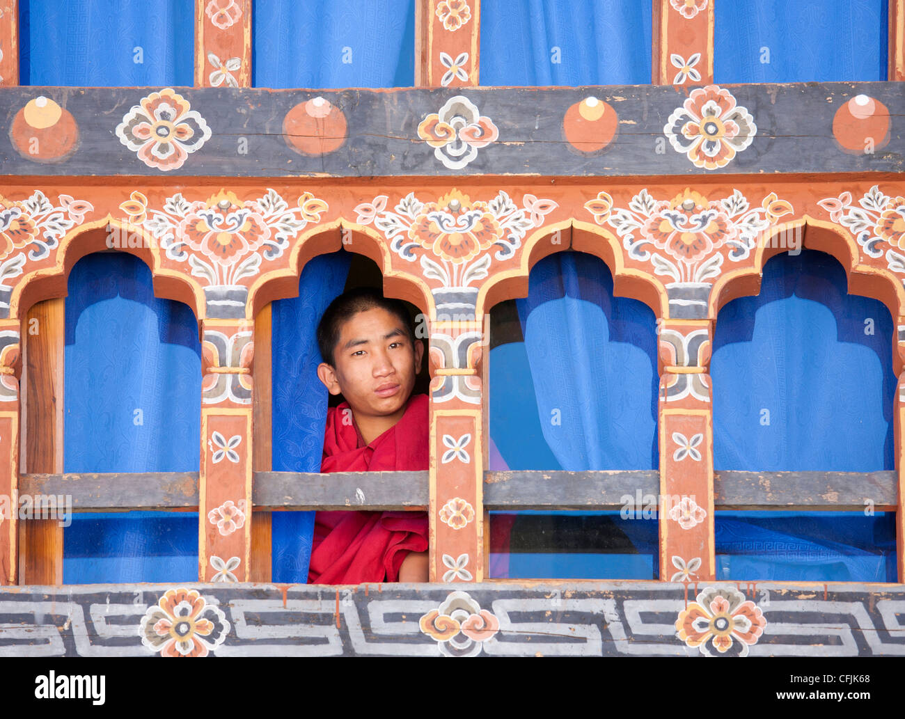 Young Buddhist monk looking out of a window at Trongsa Dzong, Trongsa, Bhutan, Asia - Stock Image