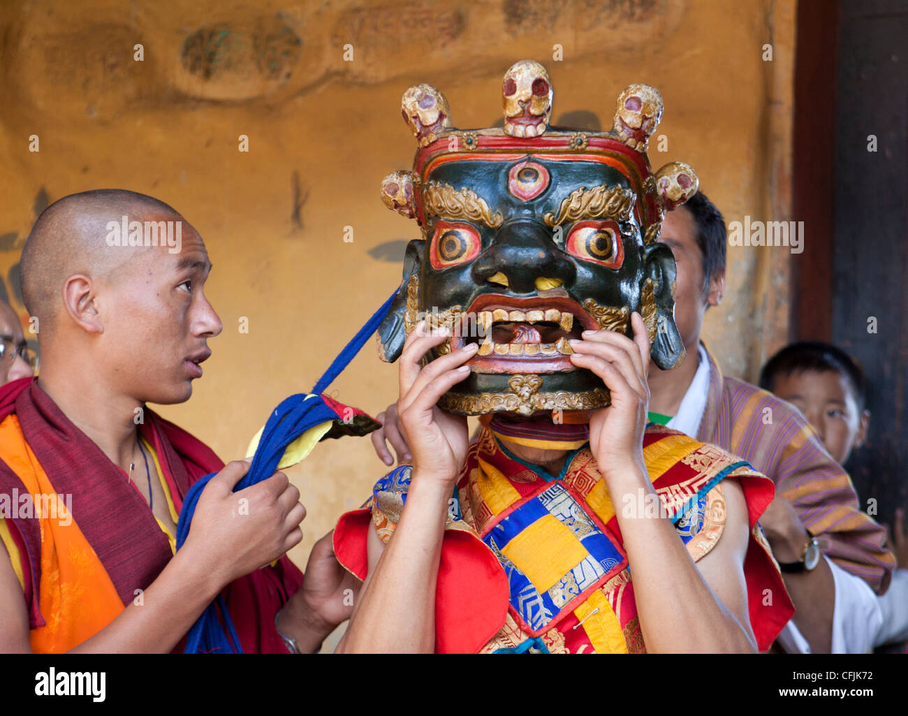 Buddhist monk being helped to secure his carved wooden mask, Jakar, Bumthang, Bhutan, Asia - Stock Image