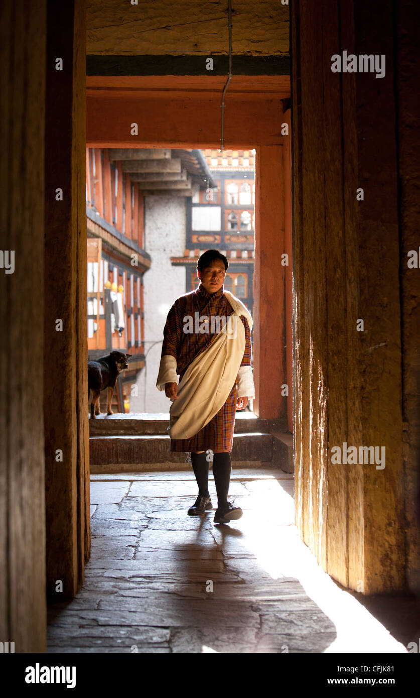 Local man in national dress backlit by evening sunlight at the Jakar Dzong, Jakar, Bumthang, Bhutan, Asia - Stock Image