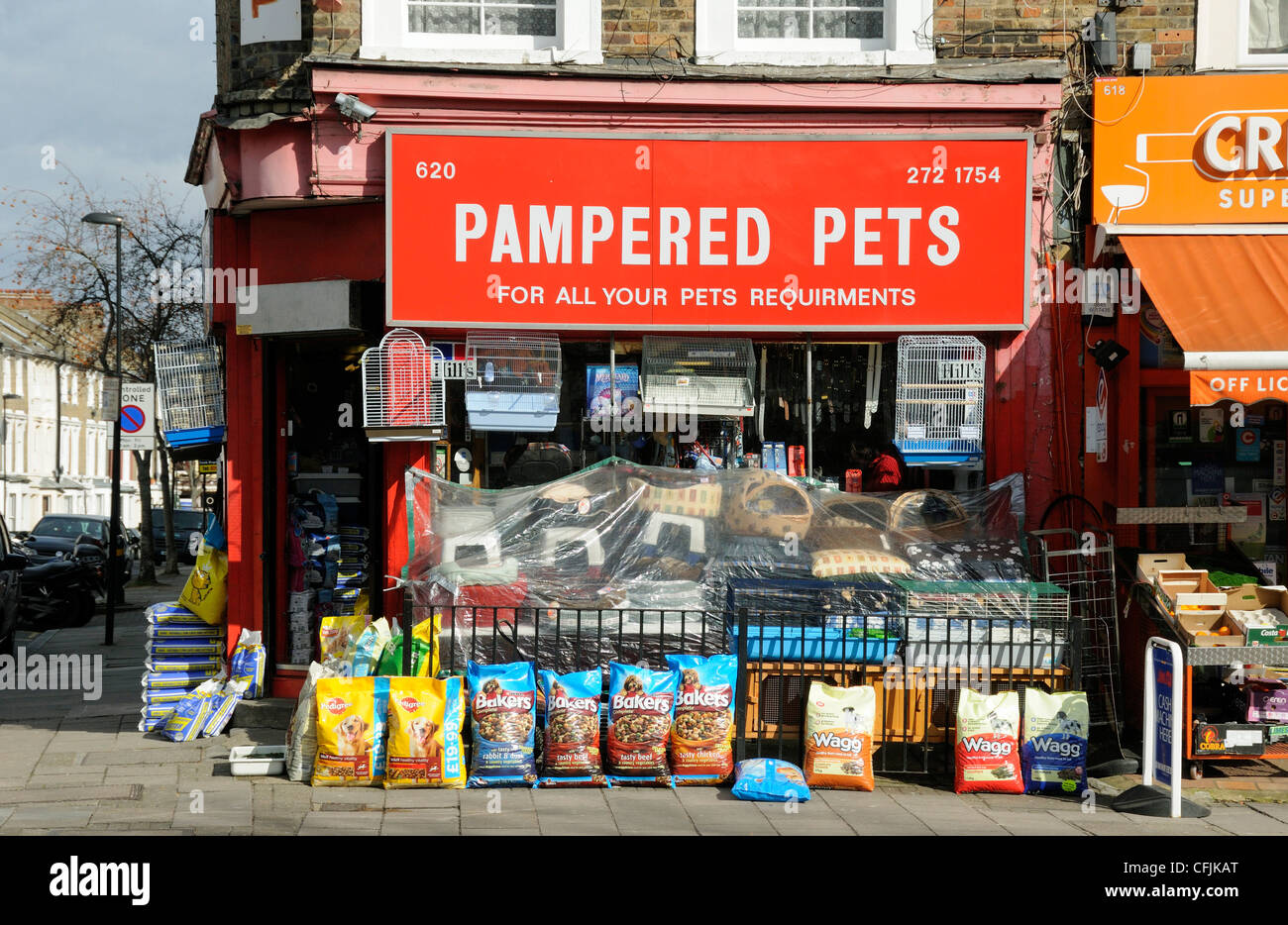 Pampered Pets, pet shop in Holloway Road with bags of food and baskets on the pavement Islington London England - Stock Image