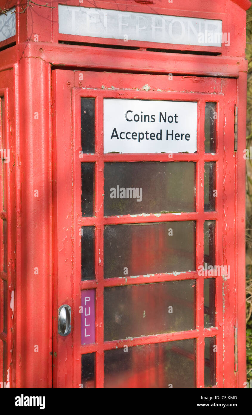 Traditional red telephone box in rural area with sign saying coins not acepted - Stock Image