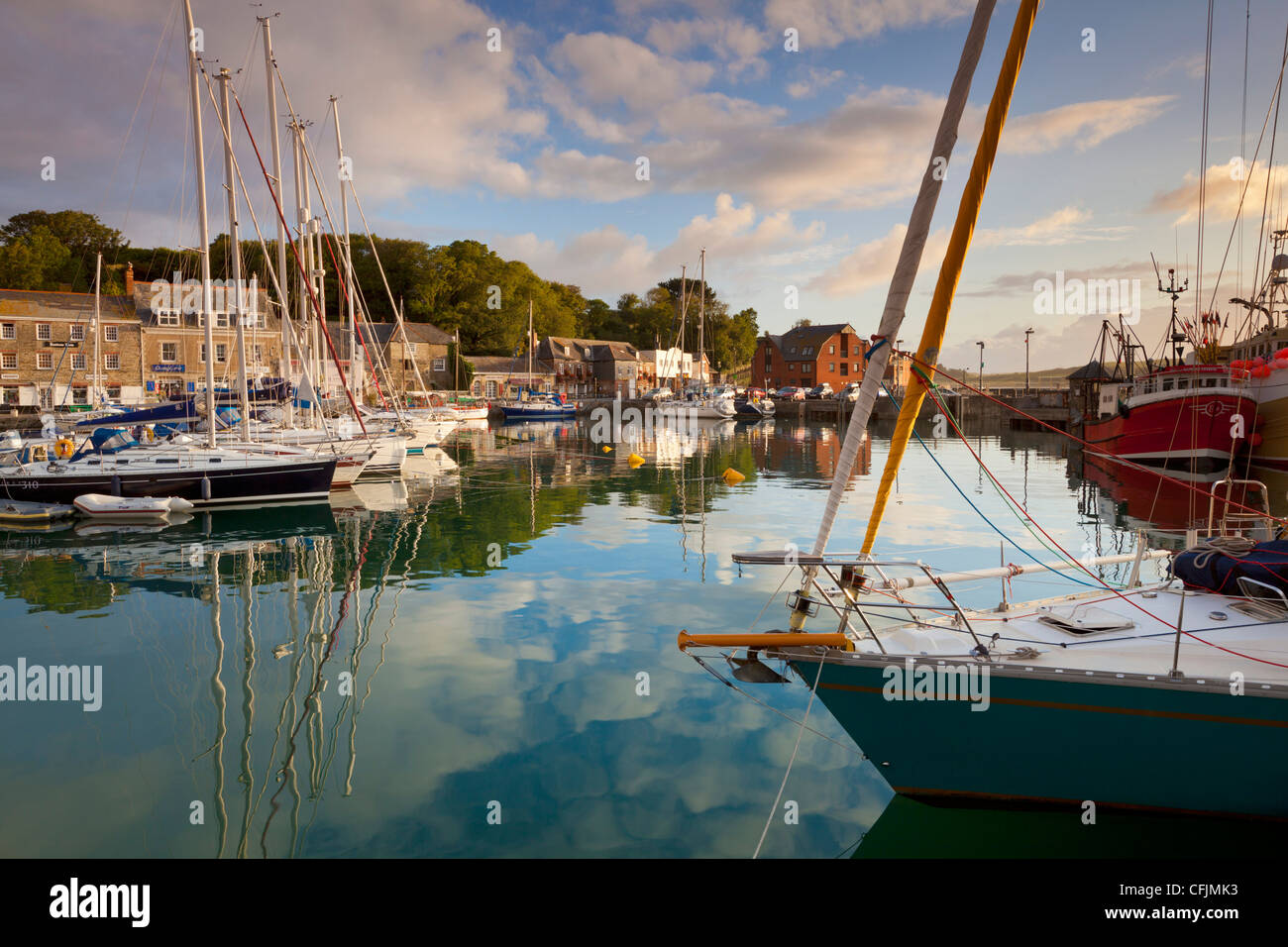Low morning light and sailing yacht reflections at Padstow Harbour, Cornwall, England, United Kingdom, Europe - Stock Image