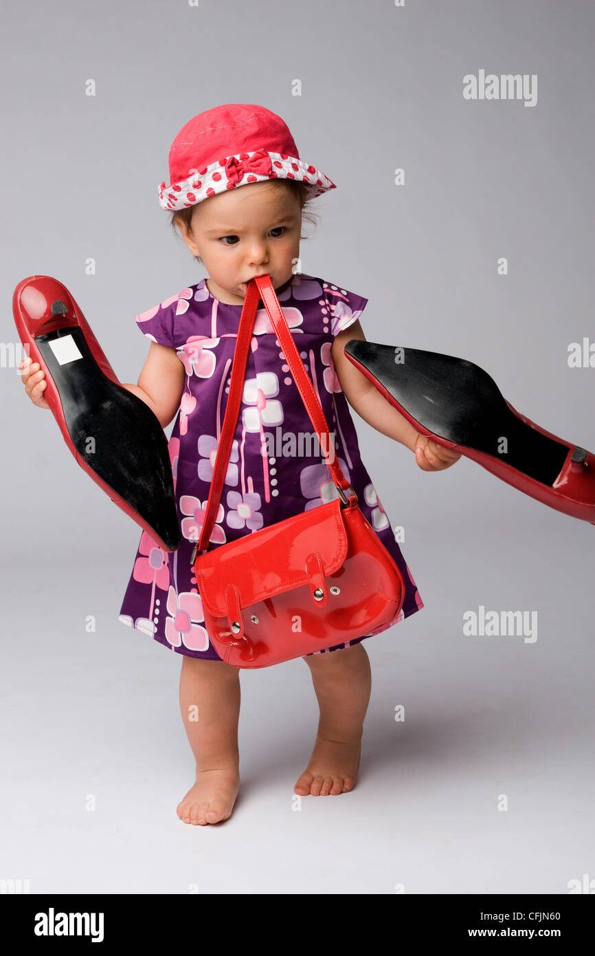 Cảm Cười...chơi - Page 40 Funny-shot-of-one-year-old-fashion-girl-with-red-purse-and-big-adult-CFJN60