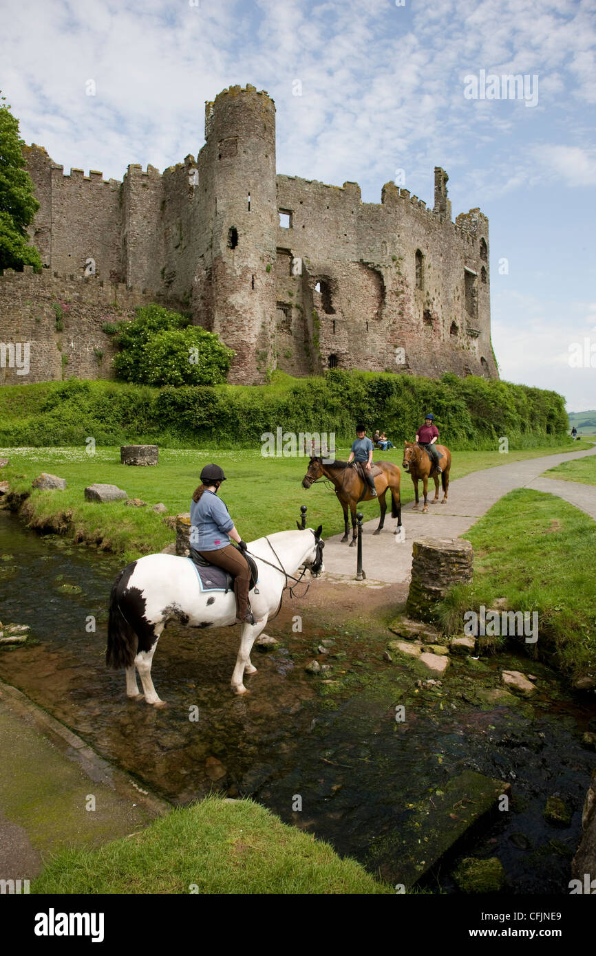 Horse riders and pony trekking across a stream in Laugharne, Camarthenshire, Wales - Stock Image