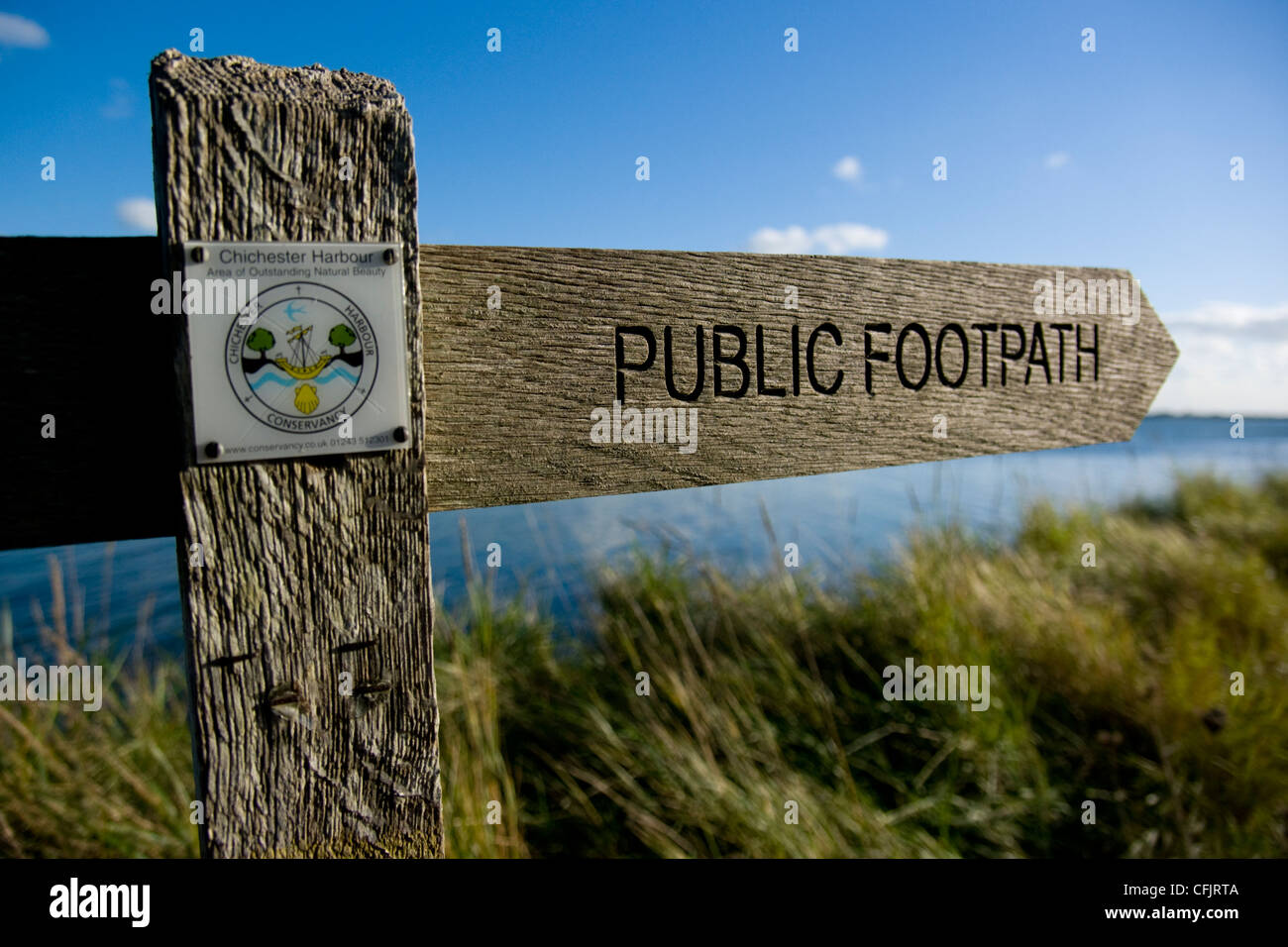 Wooden signpost pointing out the public footpath around Thorney Island - Stock Image