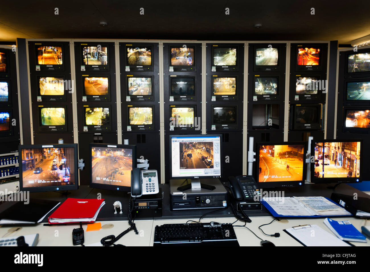 Banks of screens at a local authority operated CCTV closed circuit television suite monitoring night time activity - Stock Image