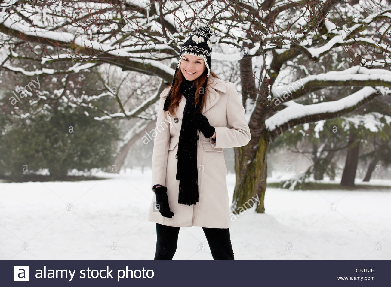 A young woman standing in the snow, smiling - Stock Image