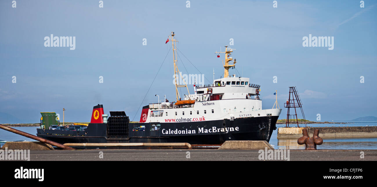 Passengers on board Cal-Mac's car and passenger ferry the M.V. Saturn (Gaelic: 'Satharn') tied up at - Stock Image