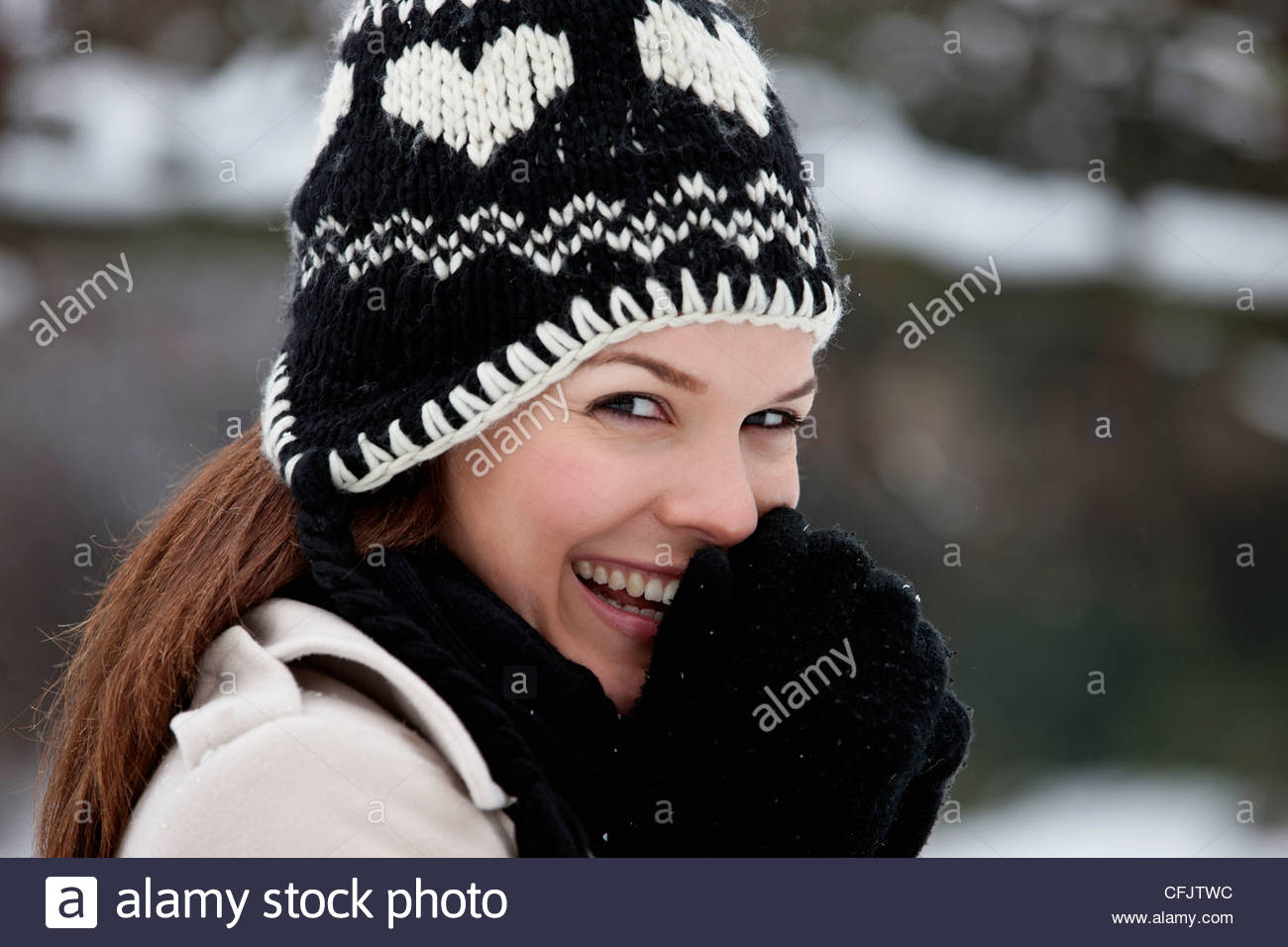 Portrait of a young woman wearing a woolen hat, trying to keep warm - Stock Image