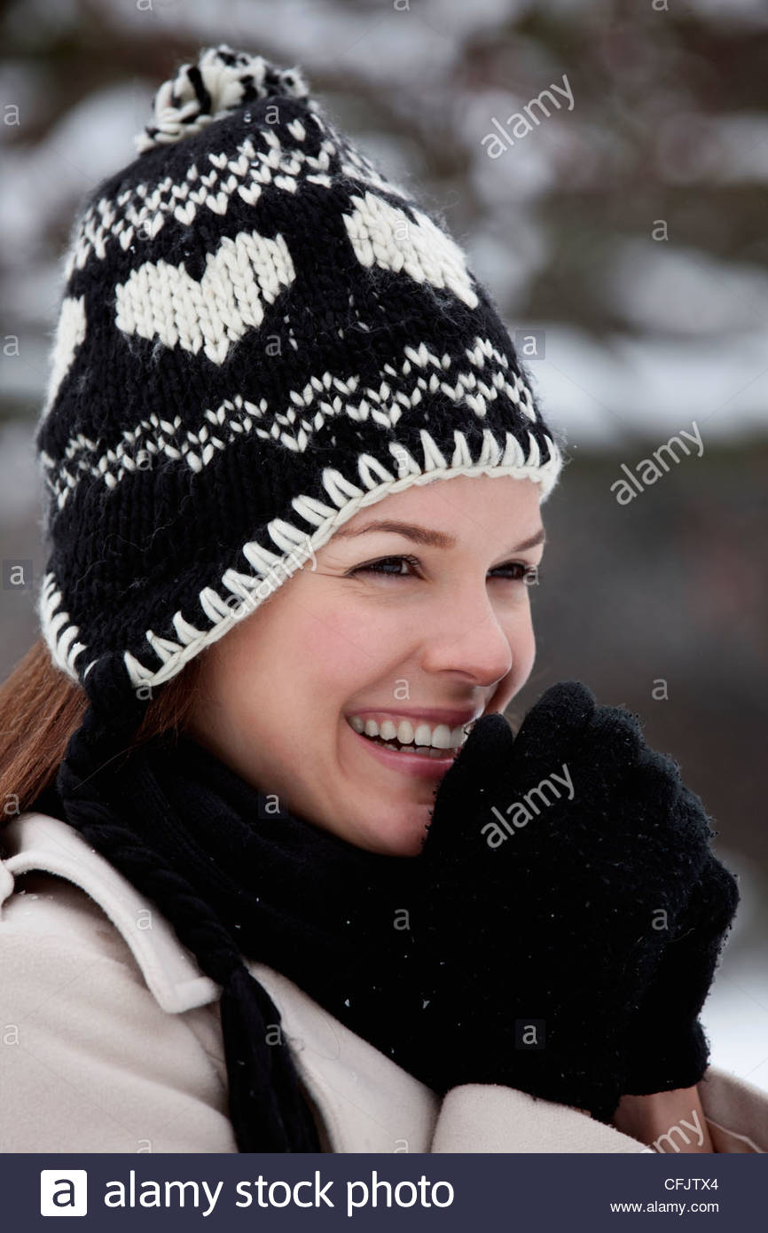 Portrait of a young woman wearing a woollen hat, trying to keep warm - Stock Image