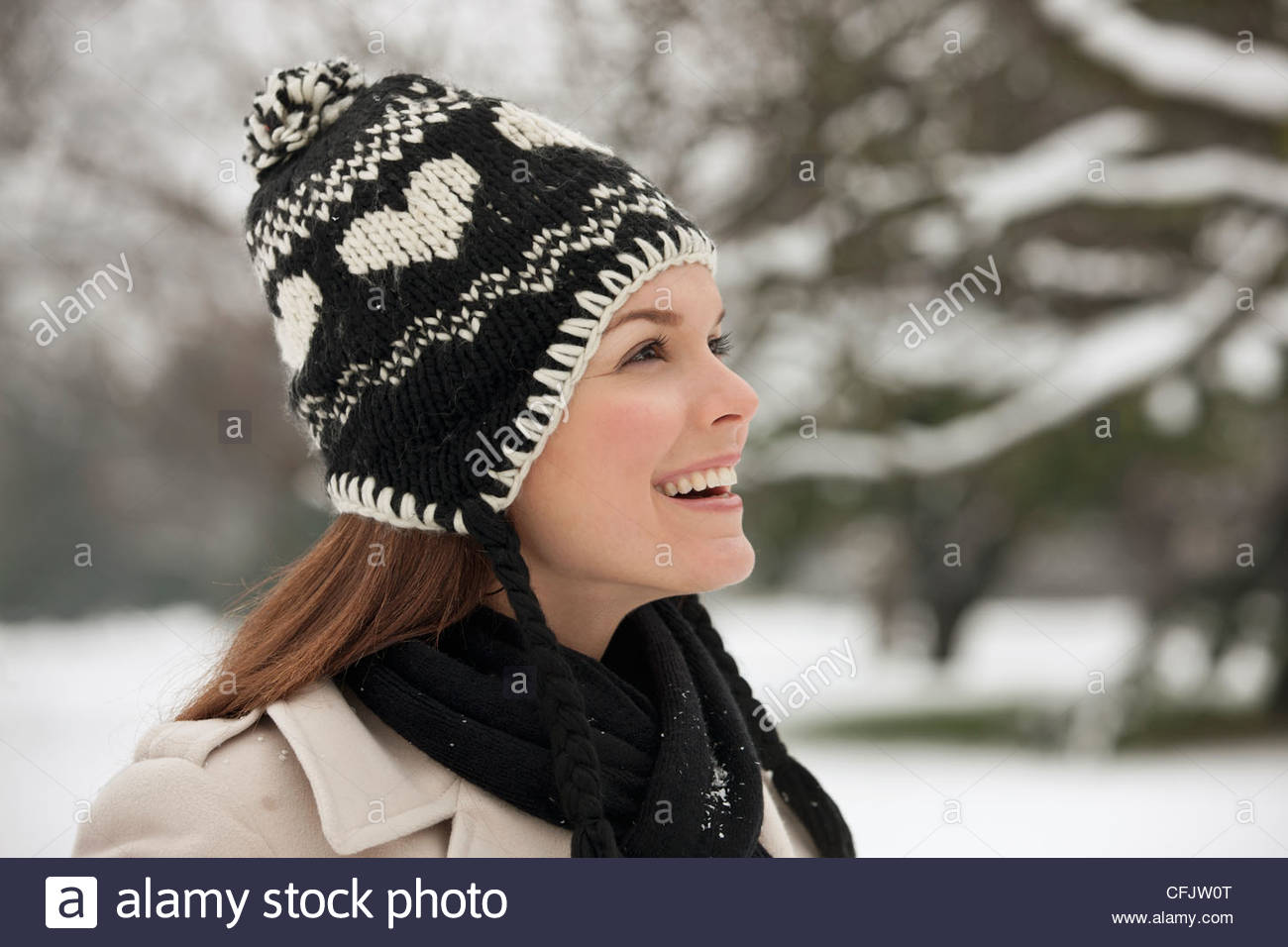 A young woman wearing a woolen hat, admiring the snow - Stock Image