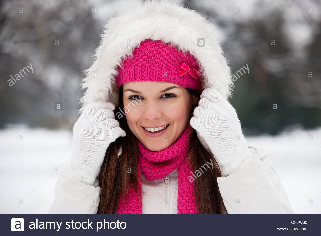 A young woman putting up the hood of her coat, smiling - Stock Image