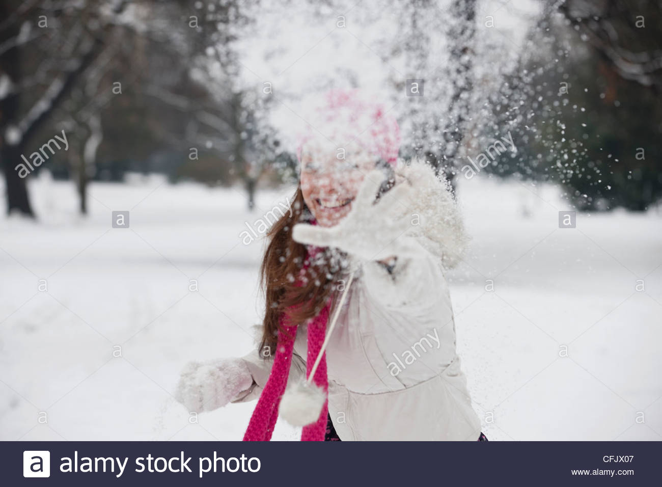 A young woman throwing a snowball - Stock Image