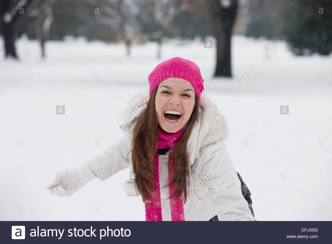 A young woman throwing a snowball, laughing - Stock Image