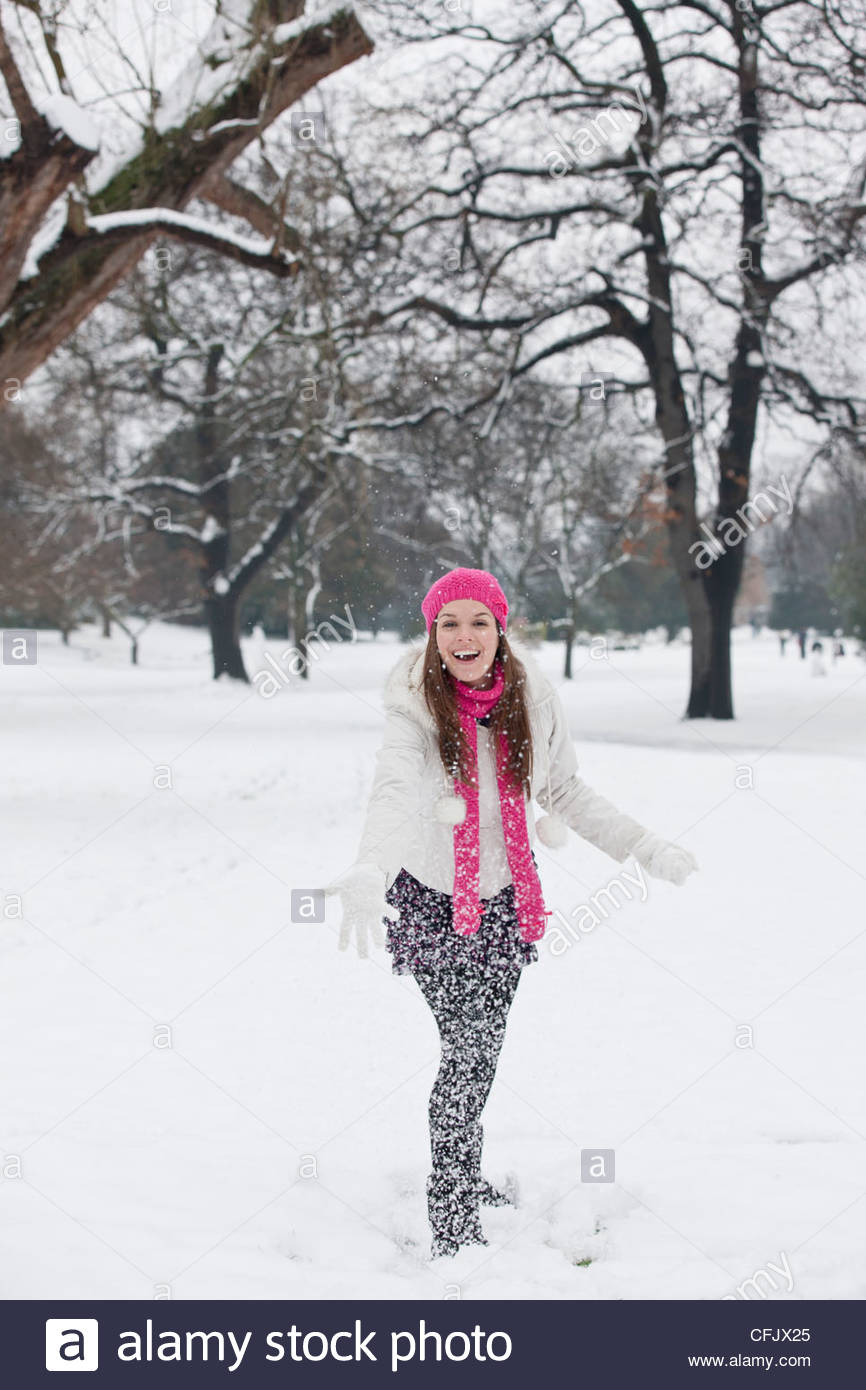 A young woman throwing a snowball, smiling - Stock Image