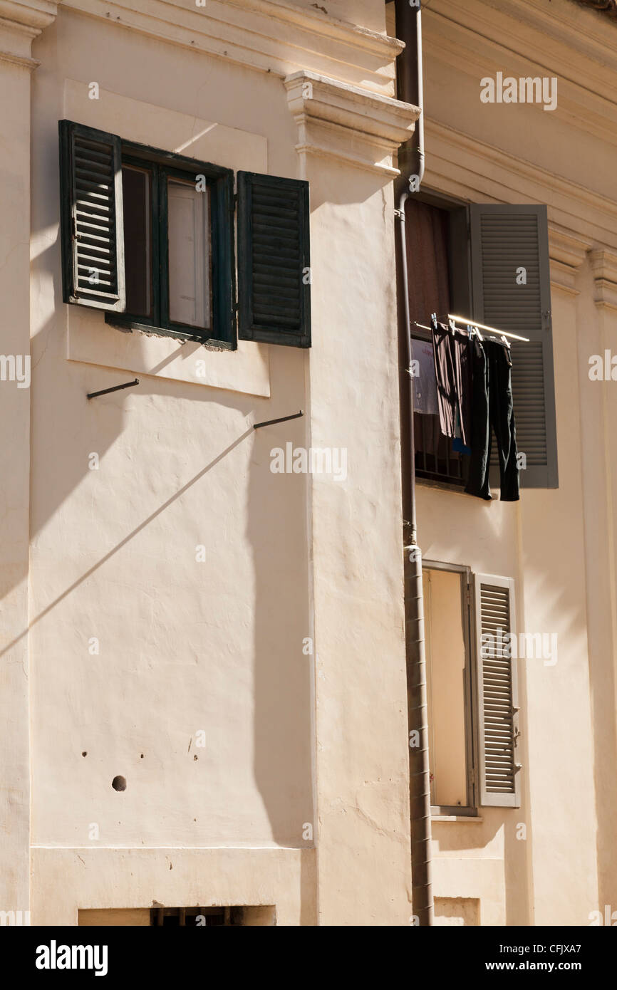 shuttered windows on italian house with sunlight and washing hung to dry - Stock Image