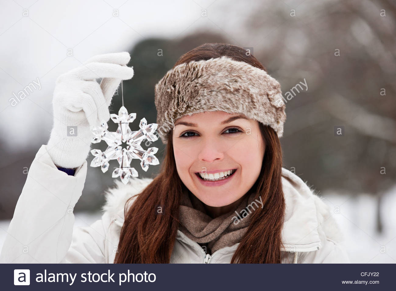 A young woman holding a snowflake decoration - Stock Image