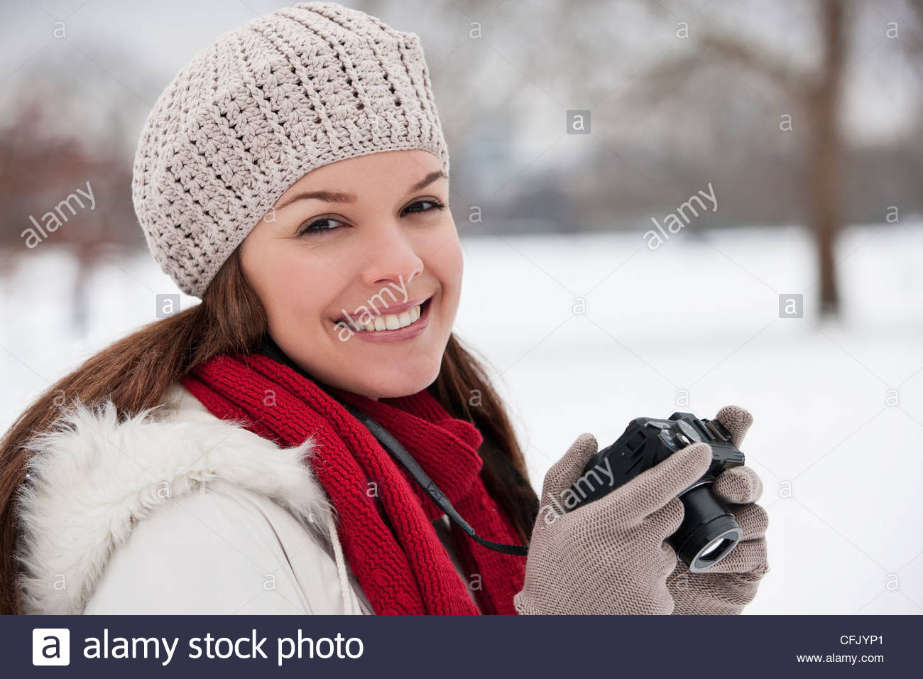 A young woman standing in the snow, holding a camera - Stock Image