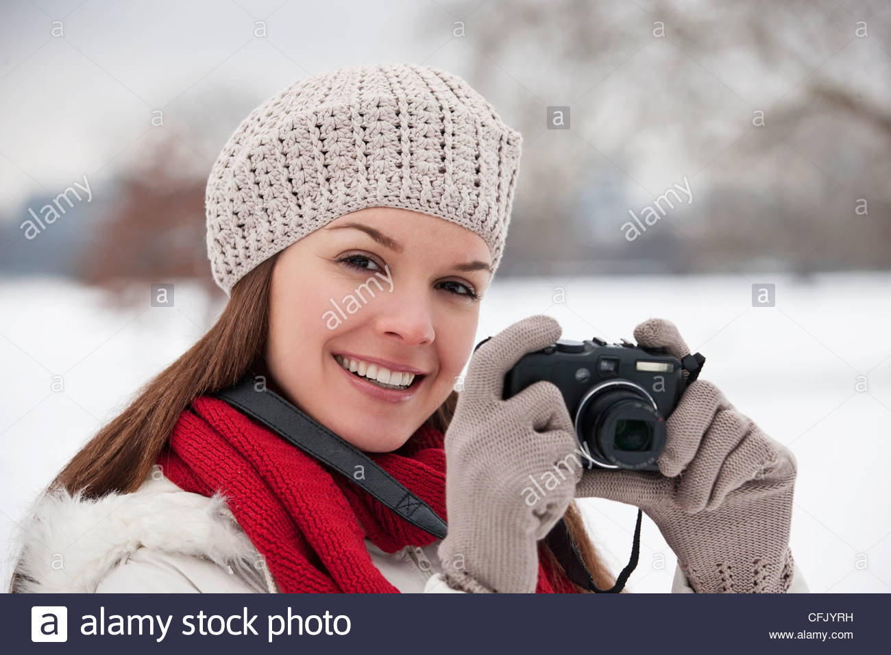 A young woman standing in the snow, taking a photograph - Stock Image