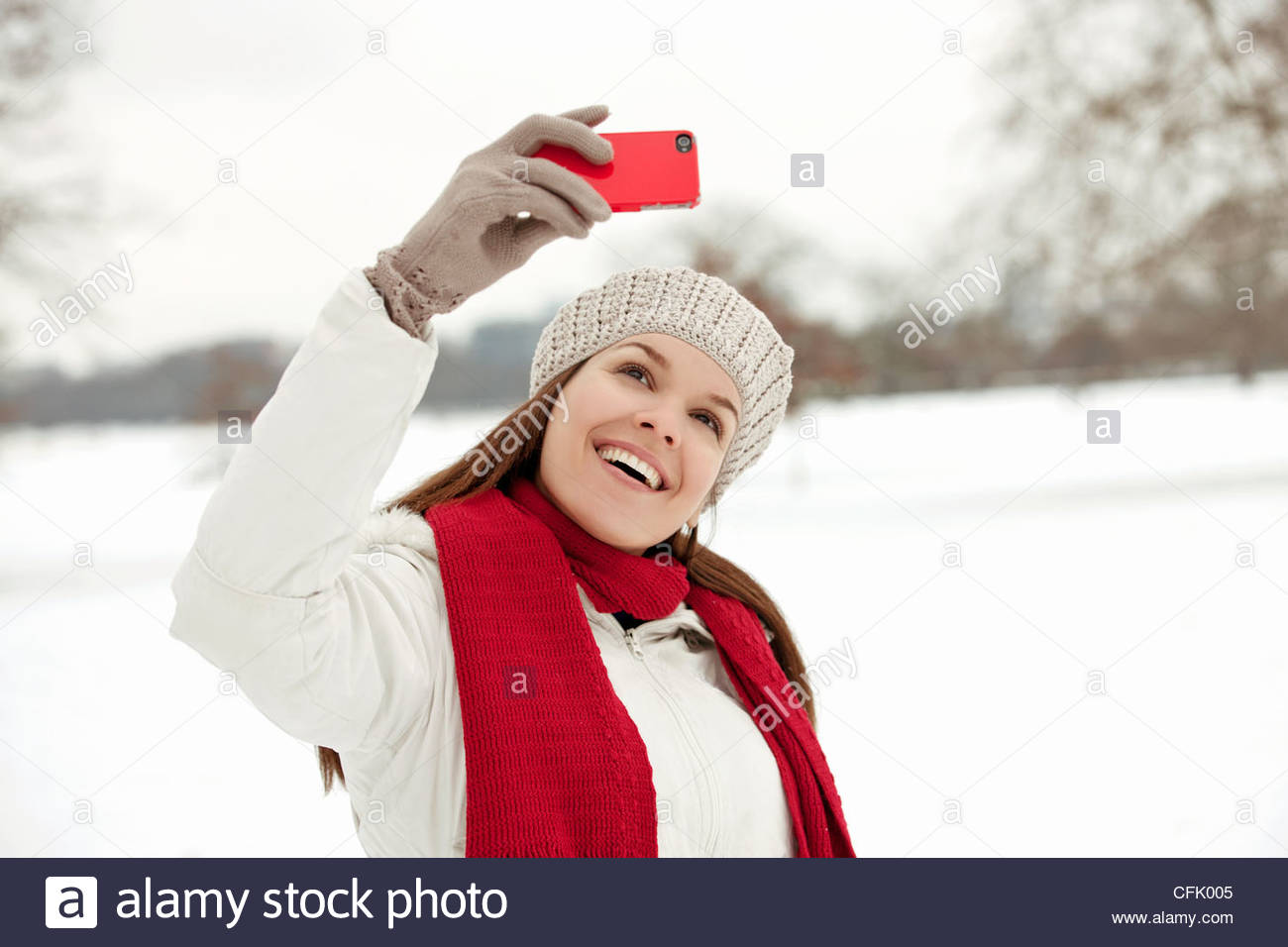 A young woman taking a photograph of herself in the snow - Stock Image