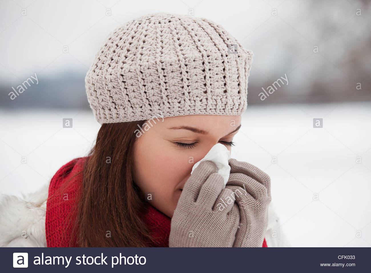 A young woman standing in the snow, blowing her nose - Stock Image